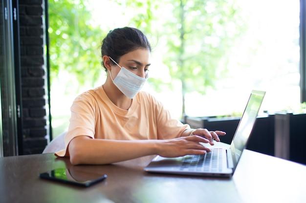 휴대 전화와 얼굴 마스크로 야외에서 노트북 작업을 하는 인도 비즈니스 여성