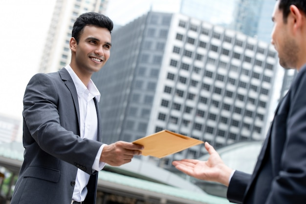 Indian businessman giving document in the envelope to his partner