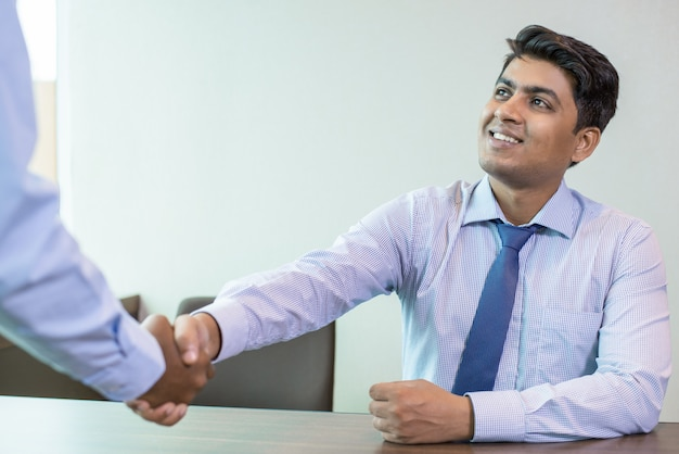 Indian businessman greeting partner in office