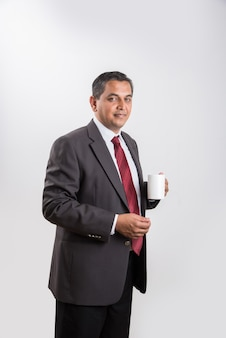 Indian businessman having coffee or tea, asian businessman and coffee or tea, businessman drinking coffee in big white cup, isolated over white background, side view