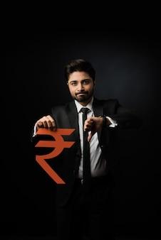 紙で作られたルピー記号を保持し、黒い背景の上に孤立して立っているインドの実業家