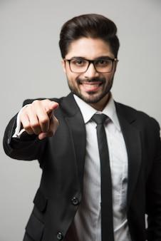 Индийский бизнесмен, указывая на вас, стоя изолированные на белом фоне