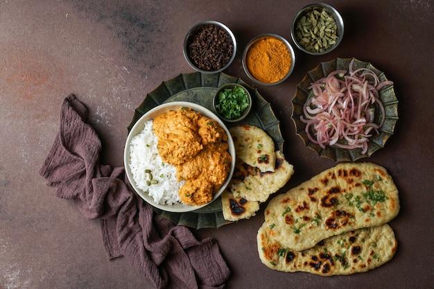 Индийский цыпленок в сливочном масле с рисом басмати, специями, хлебом наан. луковый салат Premium Фотографии