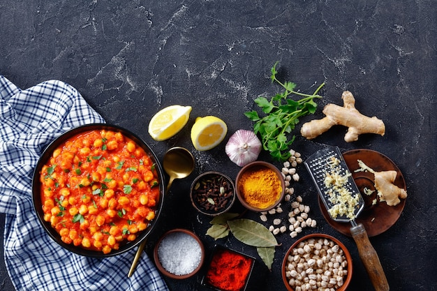 Indian chana masala or chickpea curry with ingredients on a dark concrete background