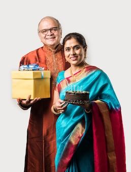 Индийская веселая пожилая пара празднует день рождения с шоколадным тортом в традиционных этнических одеждах