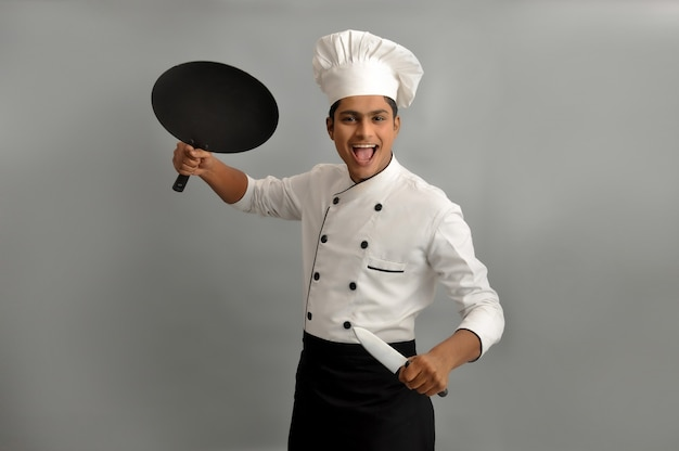 Indian chef smiling and giving action pose with his frying pan  knives