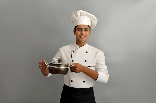 Indian chef smiling and holding pot in his hands