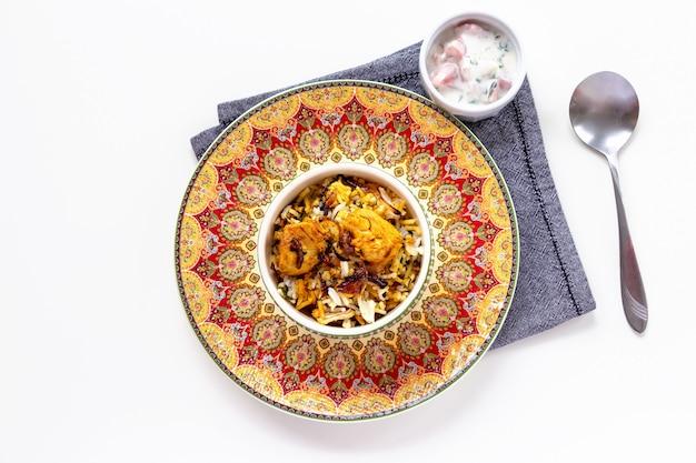 Indian chicken biryani served with yogurt tomato raita white background. selective focus.