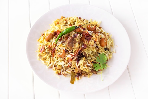 Indian chicken biryani with chili on plate white wooden background selective focus top view