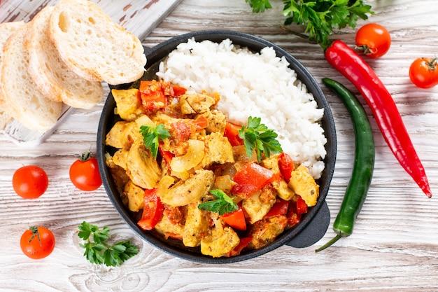 インドのチキンカレーまたはカダイチキンとライスを木製のテーブルのフライパンに入れて