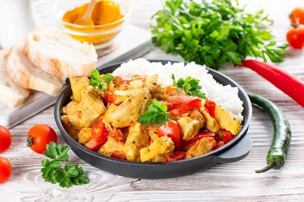 木製のテーブルの上のフライパンでご飯とインドのチキンカレーまたはカダイチキン