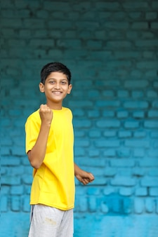Indian child giving yes gesture with hand after achievement