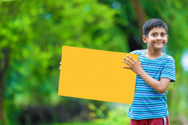 Indian child holding empty poster