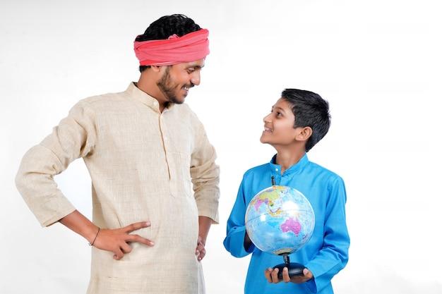 世界の地球儀を手にしたインドの子供と彼の父親がいくつかの情報を提供します。