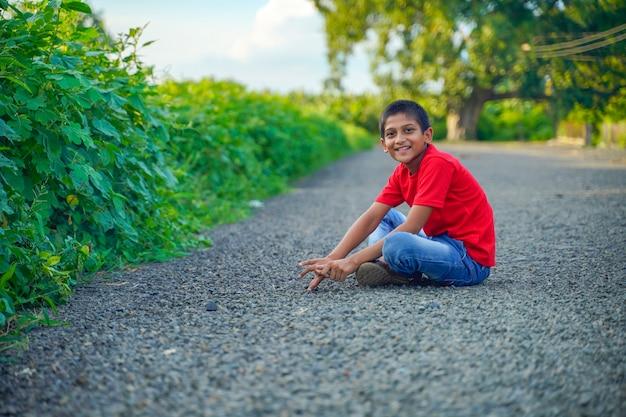 Индийский ребенок, играющий с камнем