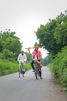 Indian child playing with toy airplane with his father on cycle