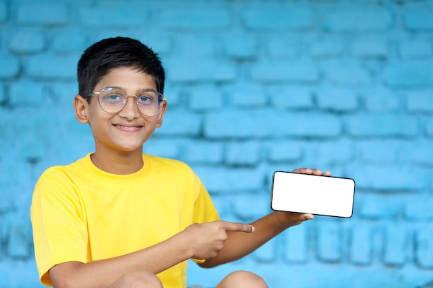 Indian child showing smartphone screen. online education concept