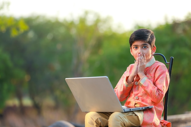 Indian child surprising on some good news in laptop