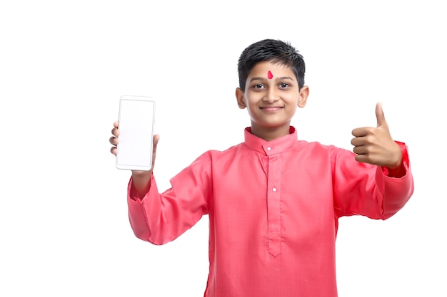 Indian child in traditional wear and showing smartphone screen on white background.