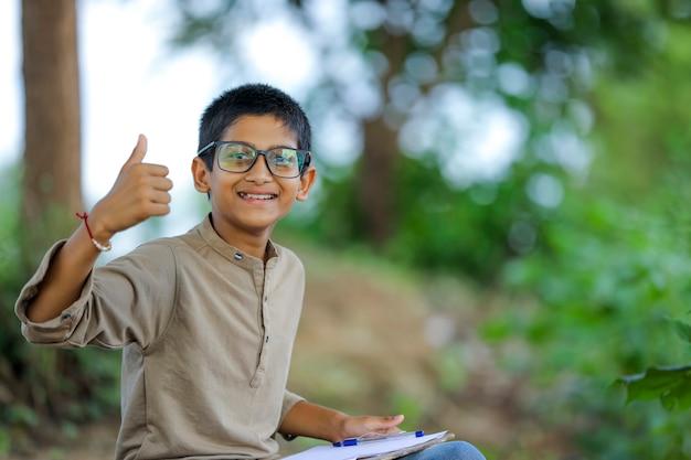 眼鏡をかけていると親指を現してインドの子供