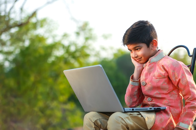 Indian child wearing traditional cloth and using laptop