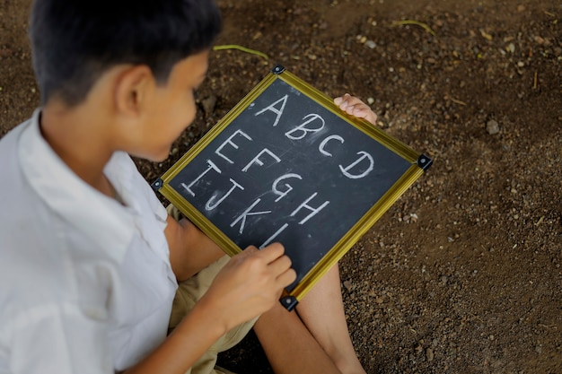 黒板にabcdアルファベットを書くインドの子供