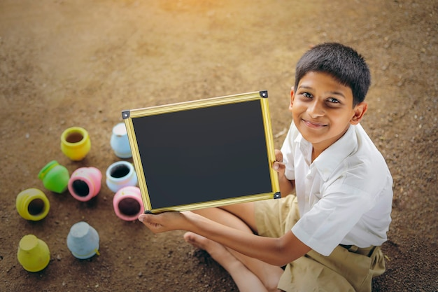 Indian child writing a b c d alphabet on chalkboard