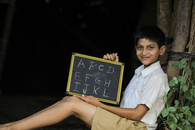 Indian child writing a b c d alphabet on chalkboard