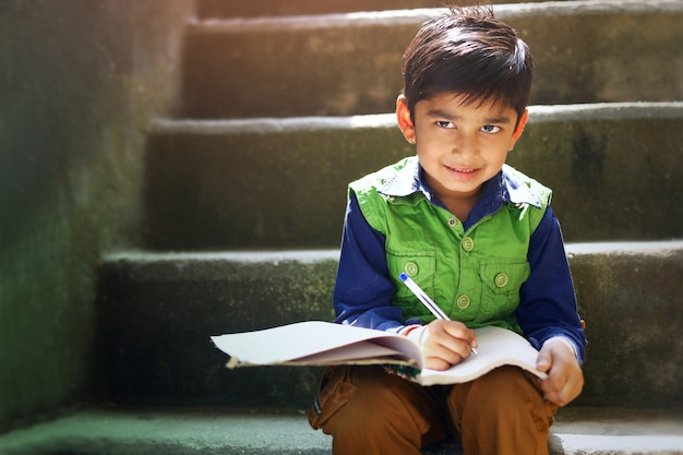 Indian child writing on note book