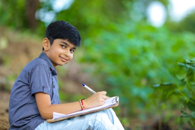 Индийский ребенок, пишущий в записной книжке
