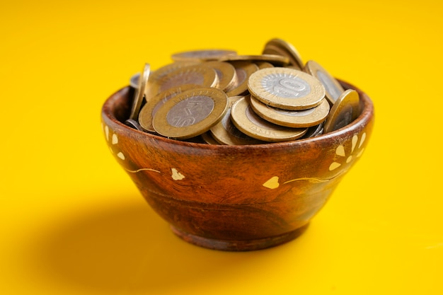 Indian coins in glass bowl on yellow surface