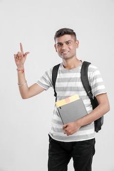 Indian college boy holding bag and books and showing direction
