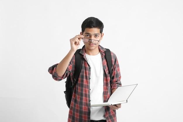 手に本を持って白い壁に立っているインドの大学生