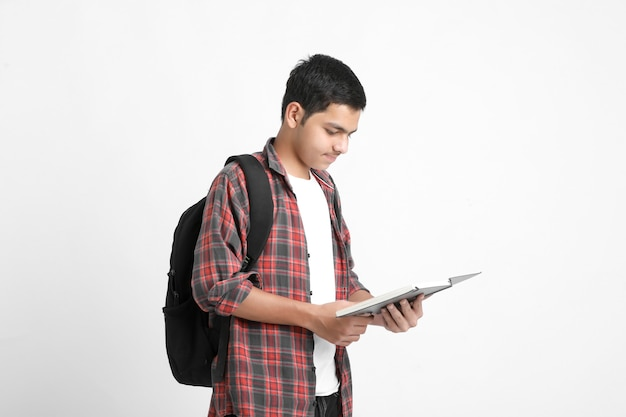 Indian college student holding schoolbag and reading book on white wall