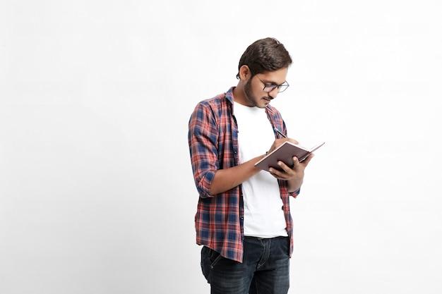 Индийский студент колледжа читает книгу на белой стене