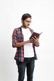 Indian college student reading book on white wall