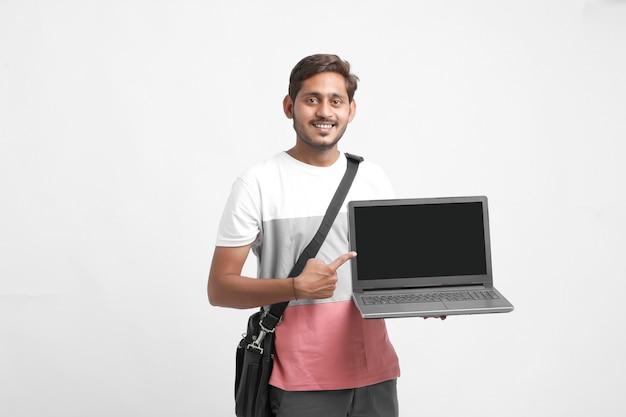 Индийский студент колледжа показывая экран компьтер-книжки на белой предпосылке.