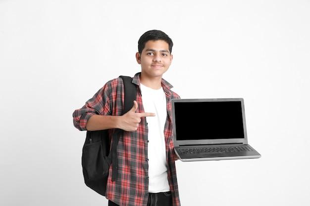白い壁にノートパソコンの画面を表示するインドの大学生
