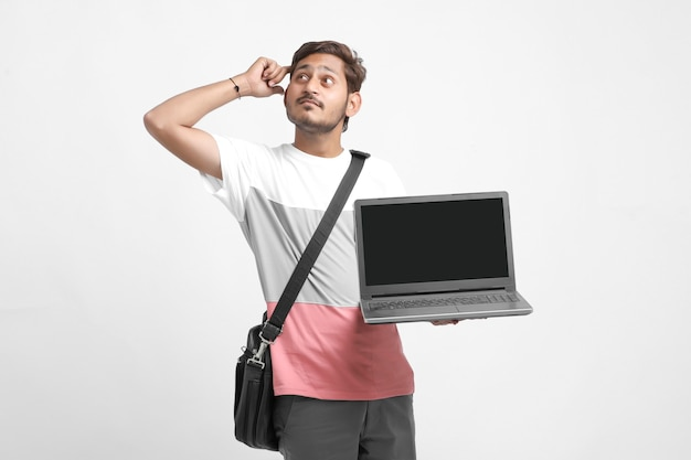 Indian college student showing laptop screen on white background.