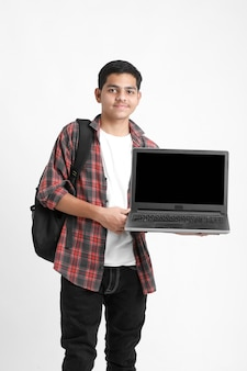 Indian college student showing laptop screen on white wall