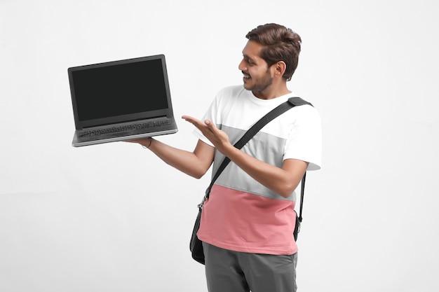 Индийский студент колледжа показывает экран ноутбука