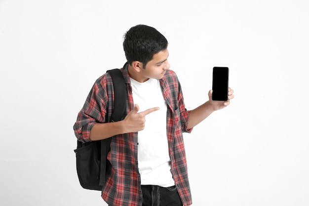 Indian college student showing mobile screen on white wall