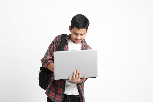 Indian college student using laptop on white wall