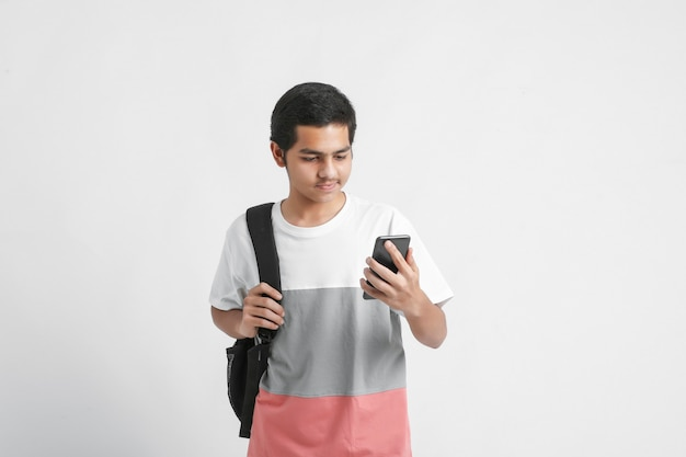 Indian college student using smartphone on white wall