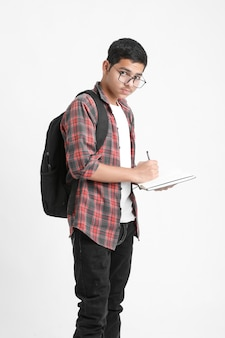 Indian college student writing some notes in notebook on white wall
