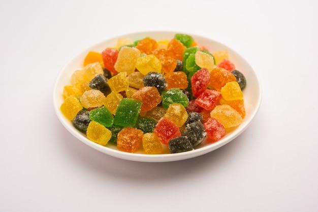 インドのカラフルなキャンディーとゼリーが砂糖でコーティングされた甘いフルーツ風味の菓子をかみ、プレートまたはボウルで提供