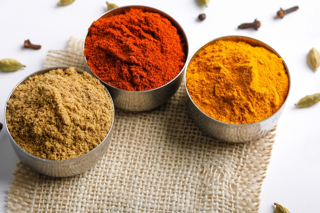 Indian colourful spices red chilli powder, turmeric powder, coriander powder on white table