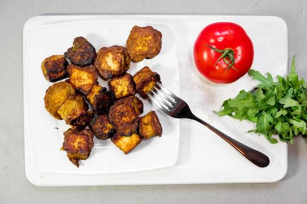 토마토와 로큘라를 곁들인 접시에 인도 코티지 치즈 조각