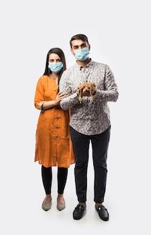 Индийская пара держит золотые украшения, украшения в медицинской маске для лица во время пандемии короны или covid-19