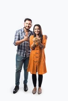 Индийская пара держит золотые украшения, украшения
